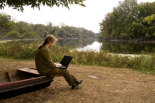 A man is working with her nootebook in outdoors