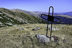 Black metal cross on an alpine meadow overlooking mountains