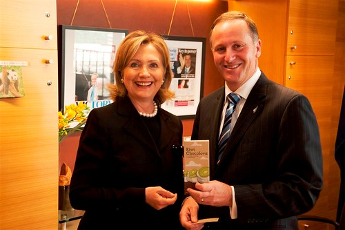 New Zealand Prime Minister Key Displays a Kiwi Chocolava Bar Beside Secretary Clinton