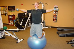 Swiss Ball balance work with side raises for shoulders