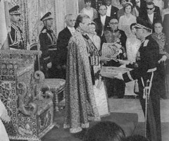 In these two pictures, the moment the Shah of Iran places the Pahlavi Imperial Crown on his head, while an officer carrying the Imperial Sceptre on a cushion approaches (below).
