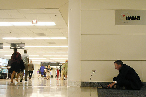 a man charging a device at an airport