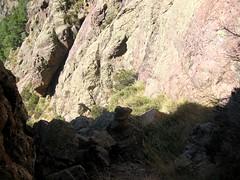 Trace cairnée de Tana di l'Orsu : les couloirs herbeux dans la descente de la falaise
