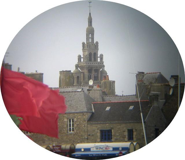 Roscoff - Le clocher et les drapeaux rouges d'un bateau