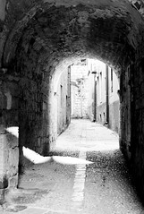 ruins(0.0), alley(0.0), arch(1.0), white(1.0), monochrome photography(1.0), air-raid shelter(1.0), monochrome(1.0), black-and-white(1.0), black(1.0), infrastructure(1.0),