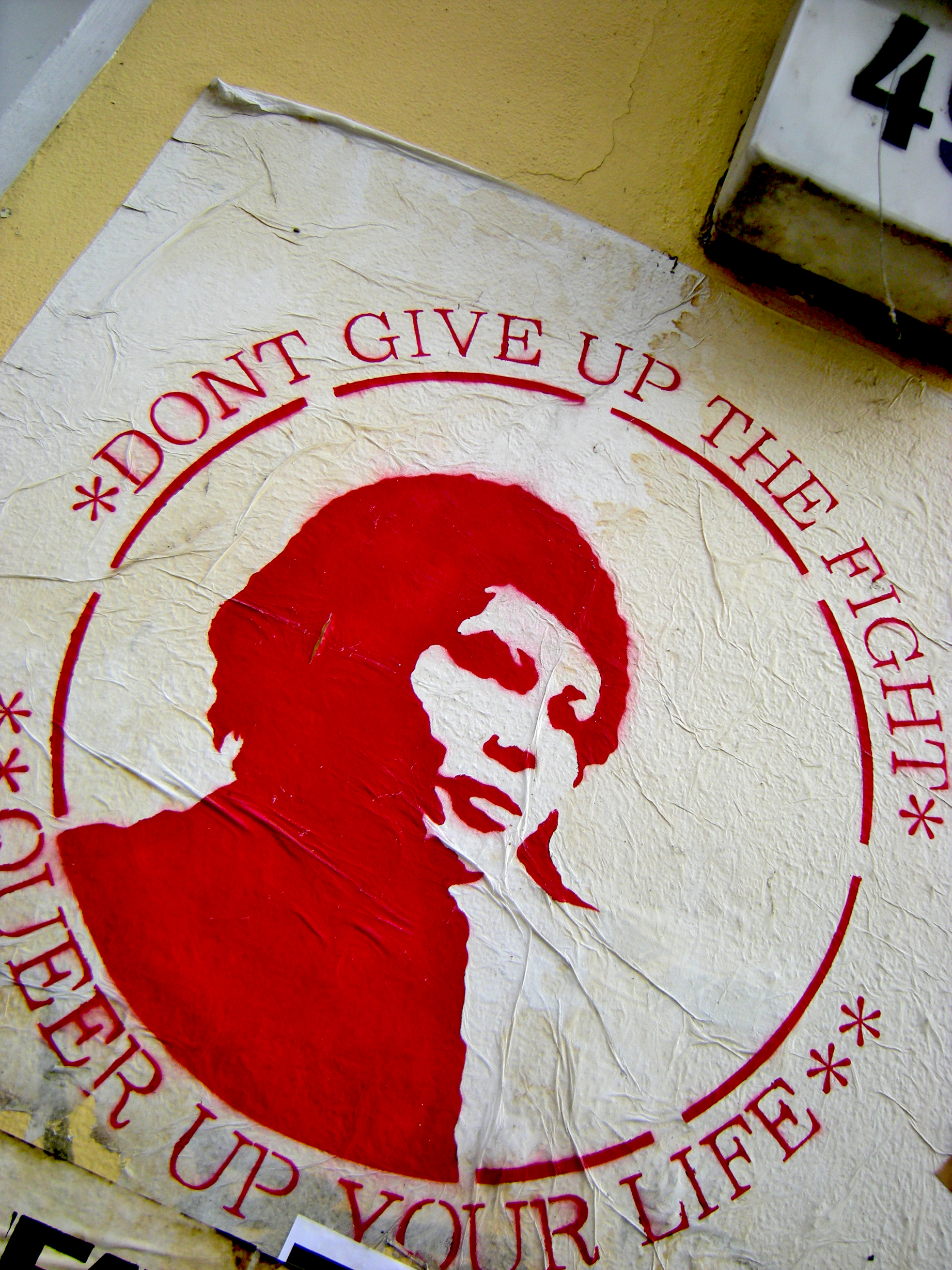 "[Photo description: a red and white sticker, young woman's face in profile surrounded by a red circle and the words ""Don't give up the fight - Queer up your life""]"