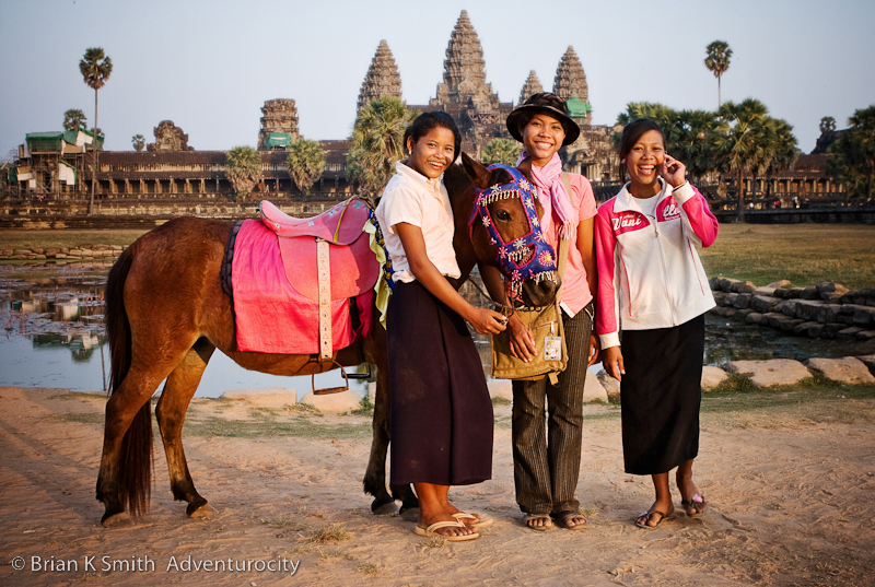 Three Khmer women with a horse pose for a photo in front of Angkor Wat.