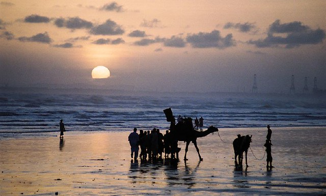 camel ride on Sandspit Beach by CC user murtazabravo on Flickr
