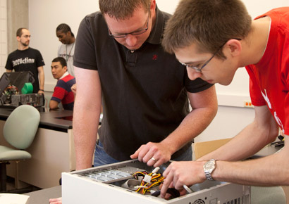 Newman University students fixing computers in class