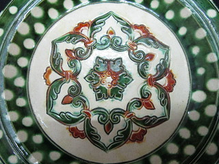 A Tang Sancai Pottery Dish with six-petalled 'Bao Xiang Hua' Blossoms and milk-white colored Spots on green Ground Design 唐三彩六瓣寶相花及綠地奶白色斑點紋盤 | by Orion Museum
