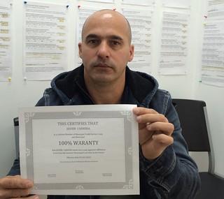 Javier Carrera muestra su certificado de afiliacion con covertura de por vida con Municipal Credit Service Corp