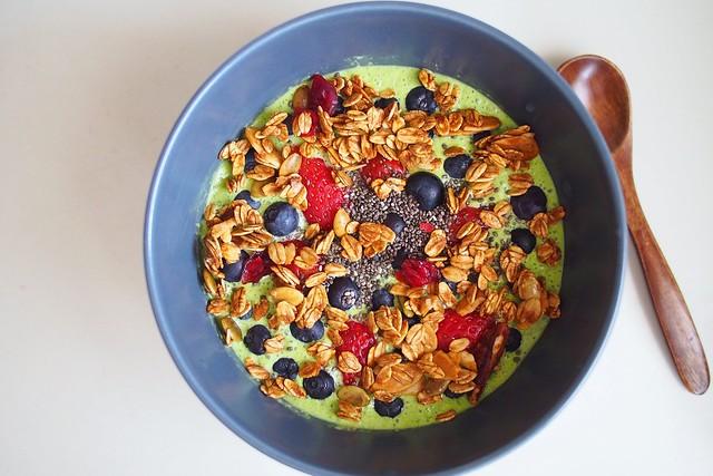 peashoot yoghurt smoothie bowl topped with strawberries, blueberries, chia seeds, homemade gula melaka granola