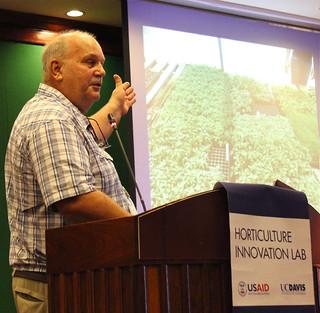 Man at podium, gesturing to image of plants behind him IMG_6506eds