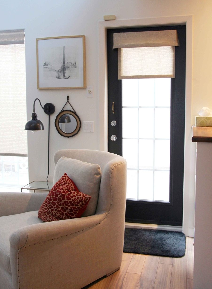 exterior door painted black in room with chair and red cushion