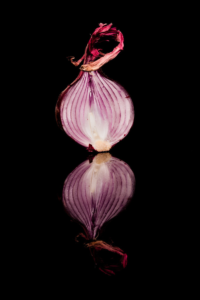 Image that shows a half onion and its reflection.