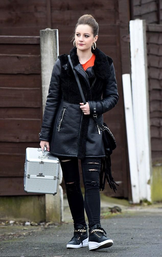 black-destroyed-jeans-black-coat-with-shearling-collar-fringe-handbag-shoulder-bag-orange-top-hi-top-wedge-trainers