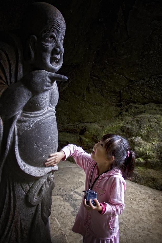 A Japanese Child Rubs A Lucky Statue In Kamakura