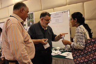 Three people engaged in animated conversation at conference IMG_6882