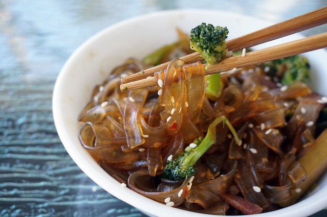 Closeup on a clump of brown, shiny glass noodles, pinched up along with a piece of broccoli by a pair of tapering chopsticks, sesame seeds sticking to the strands