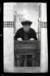 reflected self-portrait with Vest Pocket Kodak Model B camera and academic cap