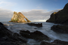 Bow Fiddle Rock, lit amber by sunset while sitting in a dark bay, Portknockie, Moray, Scotland