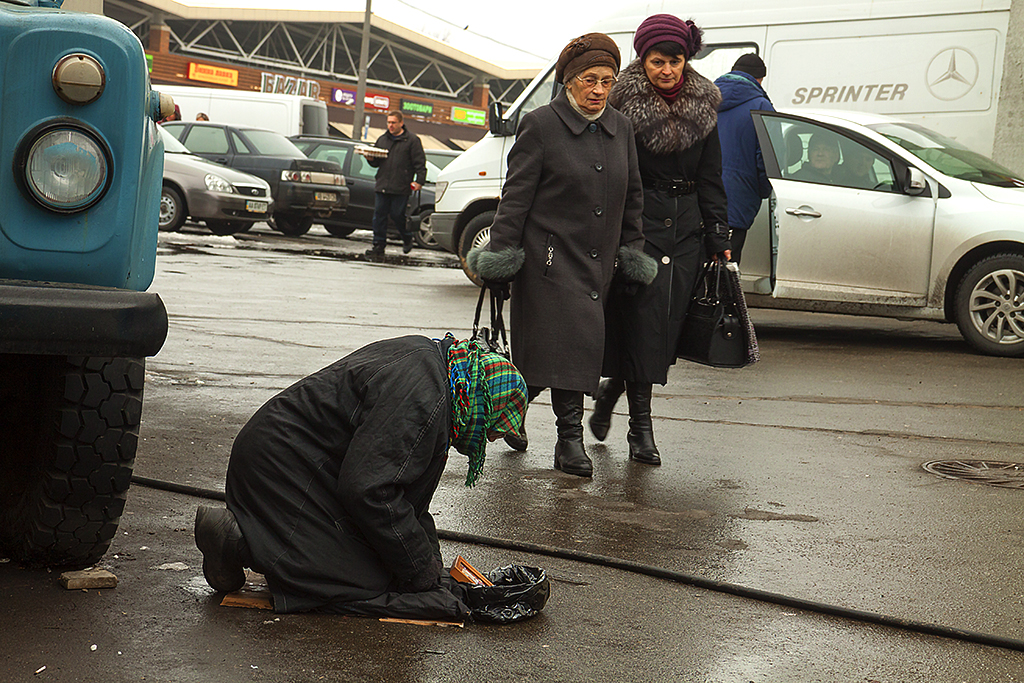 Old woman kneeling on the ground, begging--Kiev