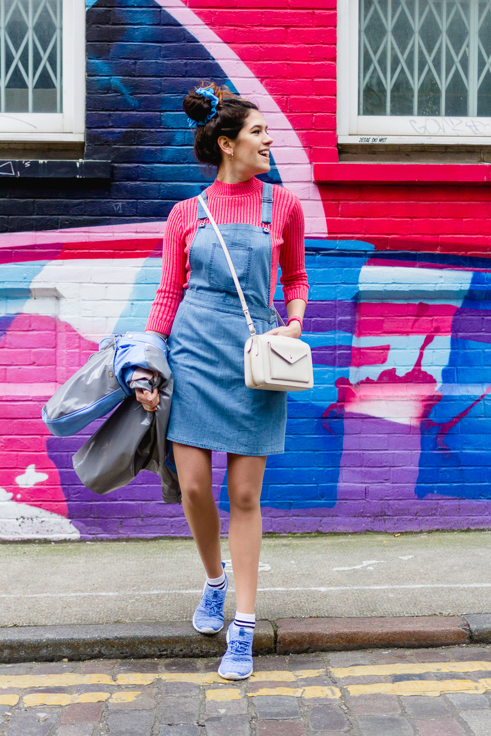 layered denim pinafore dress and pink knitted top