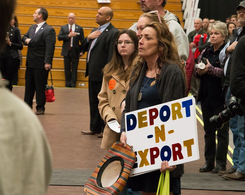Kathy Siron holding a sign that says 'deport n export'