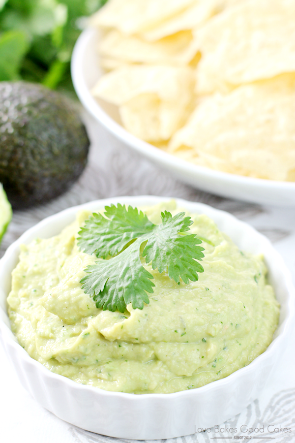 Spicy Avocado Hummus in a white bowl with potato chips.