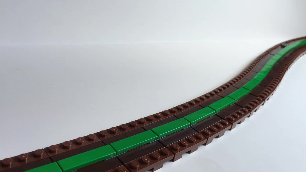 One stud wide trains: articulated magnetic coupling, flexible magnetic track, and track switch.