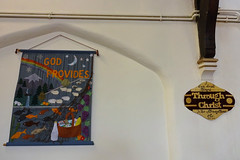 "Two wall hangings on a cream-coloured painted wall.  The one on the left is of fabric and reads ""God Provides"" along with images of sheep, fish, and a basket of groceries.  The one on the right is wooden and reads ""I can do all things through Christ who strengthens me / Phil 4.13"""