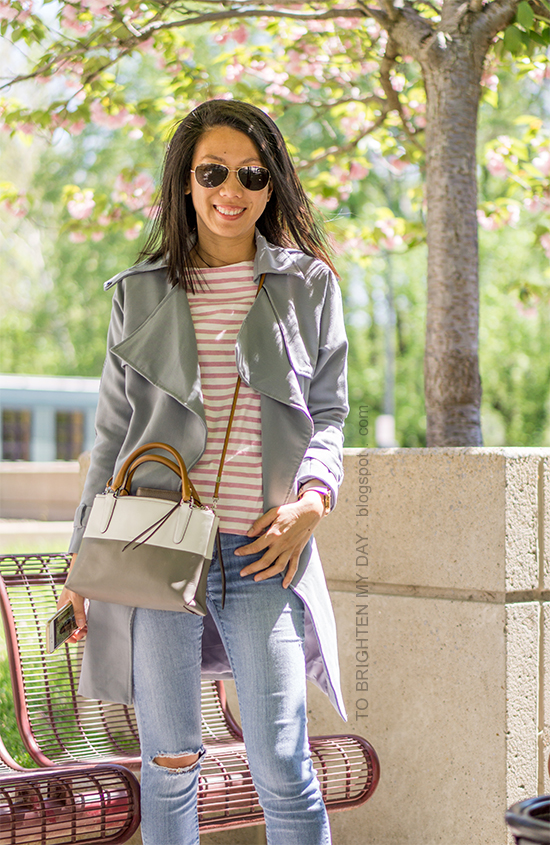blue gray drape trench coat, striped top, light wash distressed jeans, colorblocked crossbody bag