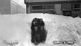 Group of people posing in snow drift in front of the barbershop after a blizzard in Kitscoty
