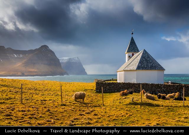 Faroe Islands - Vidoy Island - Classic view of Vidareidi church with cliffs of Bordoy and Kunoy islands