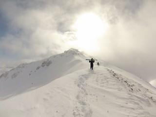 Лыжник топает на гору