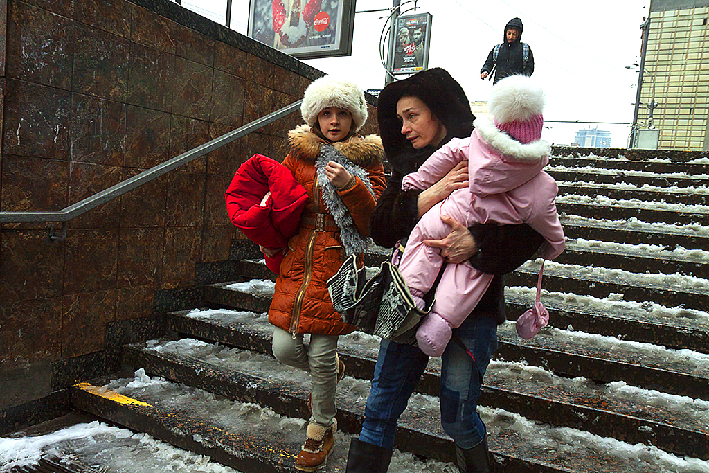 Woman holding child walking down subway entrance steps--Kiev