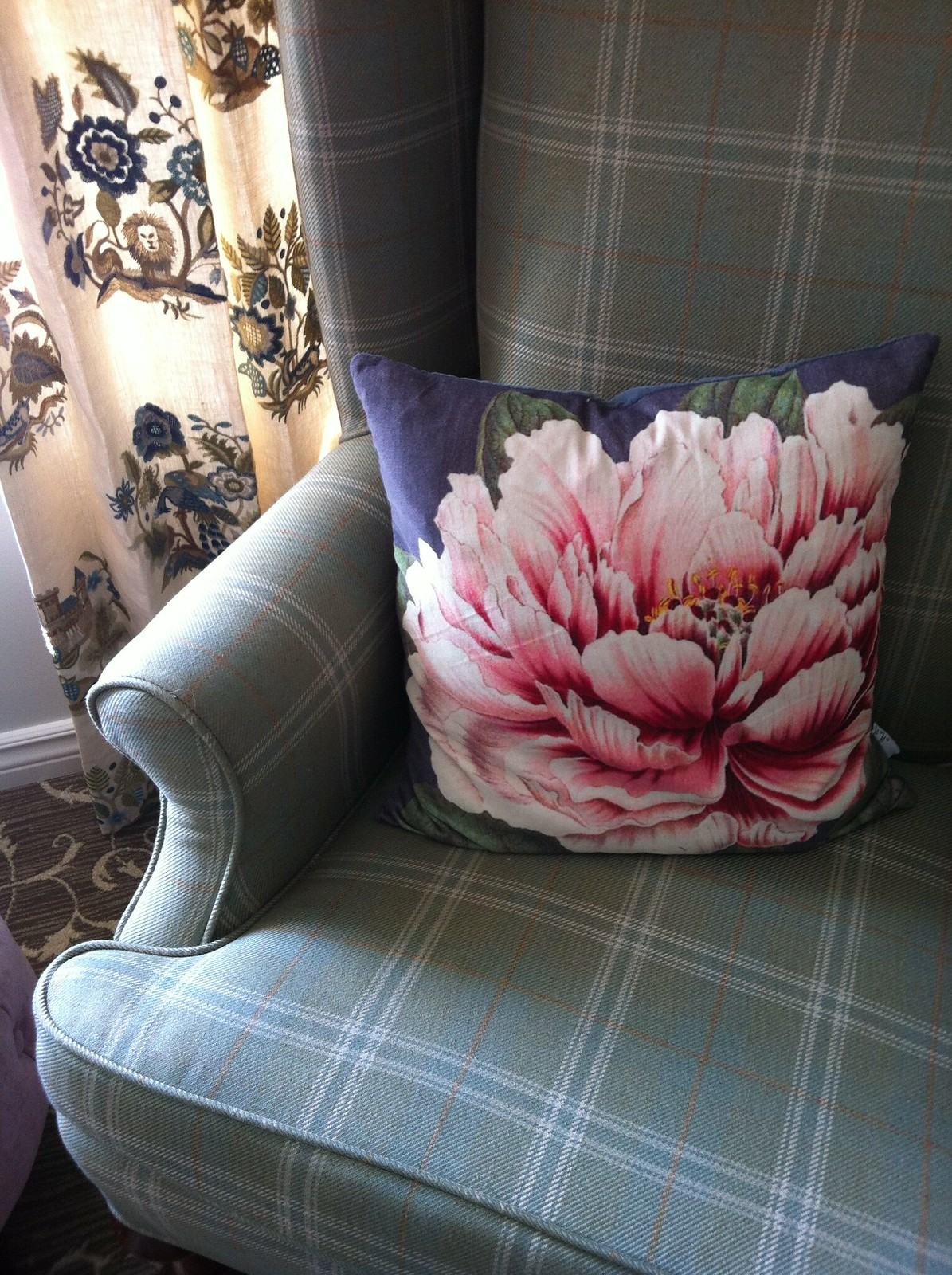 Floral cushion sitting on plaid chair in front of Cowtan and Taut draperies