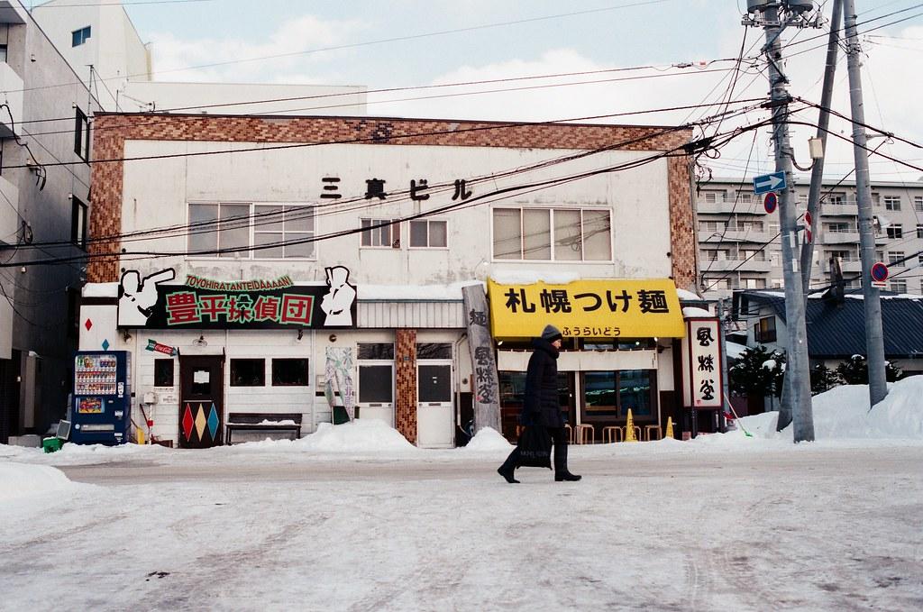 學園前 札幌 北海道 Sapporo, Japan / AGFA VISTAPlus / Nikon FM2 2016/01/31 住的地方在學園前站(gakuenmae),把行李安置好後在附近走走,但那時候南北方向搞錯了,本來想要走回大通公園,結果越走越南,之好走到下一站平岸往回搭。  一路上就隨意走走拍拍,一直觀察路上的積雪,沒有看過,所以很好奇。雪自然的堆疊起來後的表面很光滑,輕輕一碰就凹陷下去。  那時候拍到一半相機沒電,在寒冷的情況下,手不聽使喚的完成換電池的挑戰!  Nikon FM2 Nikon AI AF Nikkor 35mm F/2D AGFA VISTAPlus ISO400 8264-0027 Photo by Toomore
