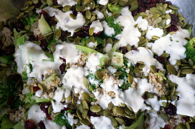 White dressing is dotted over a pile of ingredients. The shot is very close; the ingredients and dressing fill the frame entirely.