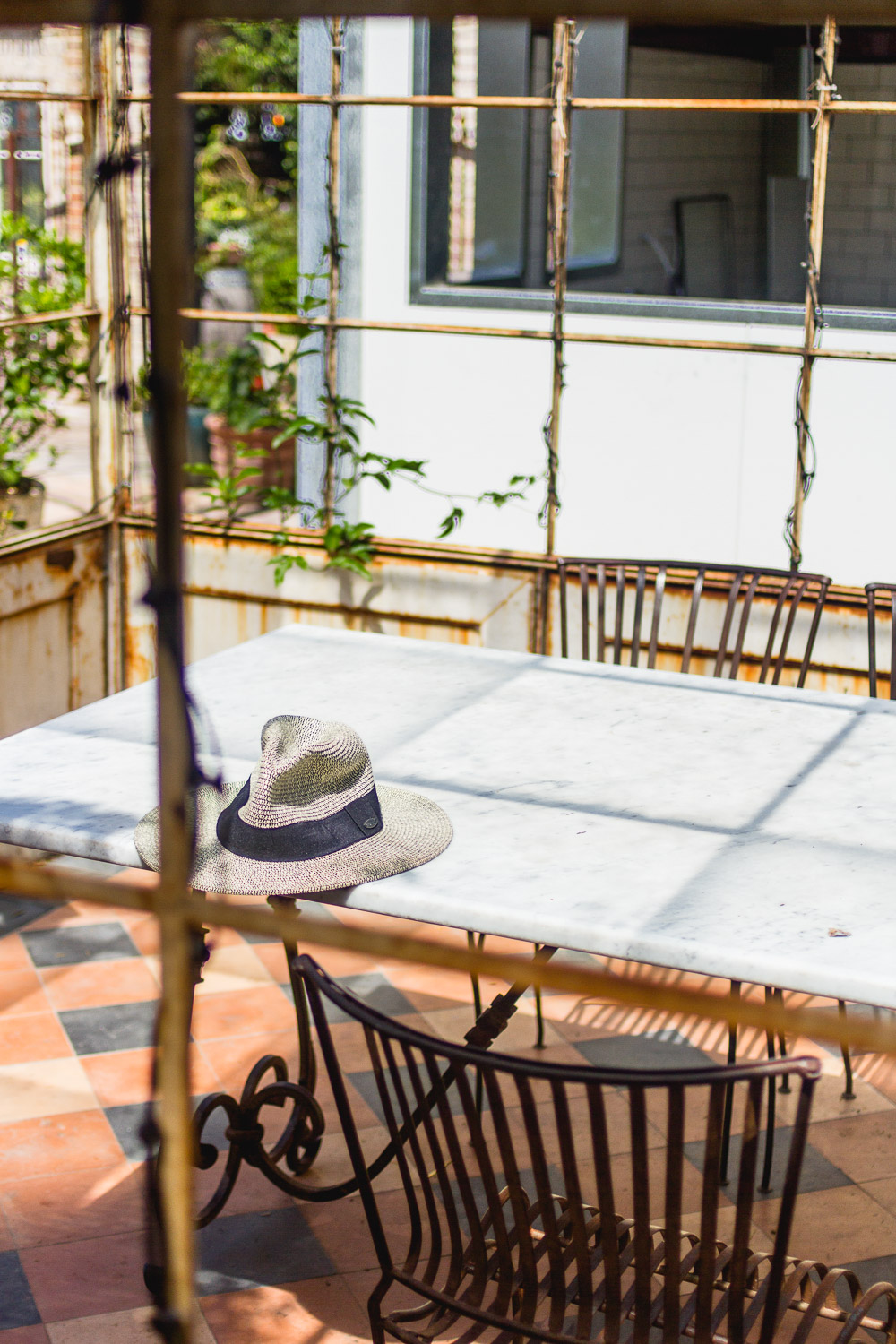 the grounds of alexandria greenhouse hat on marble table