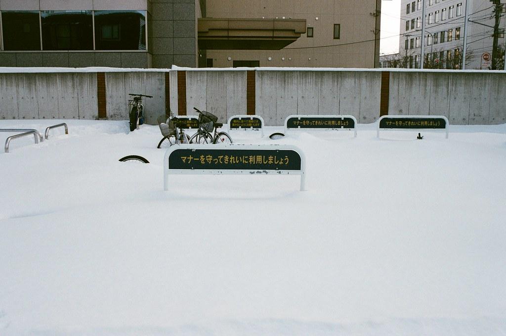 學園前 札幌 北海道 Sapporo, Japan / AGFA VISTAPlus / Nikon FM2 2016/01/31 住的地方在學園前站(gakuenmae),把行李安置好後在附近走走,但那時候南北方向搞錯了,本來想要走回大通公園,結果越走越南,之好走到下一站平岸往回搭。  一路上就隨意走走拍拍,一直觀察路上的積雪,沒有看過,所以很好奇。雪自然的堆疊起來後的表面很光滑,輕輕一碰就凹陷下去。  那時候拍到一半相機沒電,在寒冷的情況下,手不聽使喚的完成換電池的挑戰!  Nikon FM2 Nikon AI AF Nikkor 35mm F/2D AGFA VISTAPlus ISO400 8264-0025 Photo by Toomore