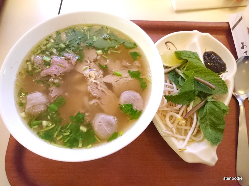 Bowl of beef pho on a tray