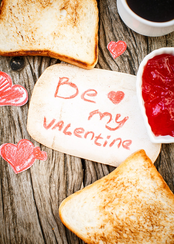 Toast with strawberry jam. Be My Valentine white message card with hand made hearts. Valentine's Day.