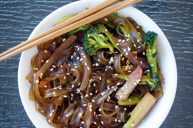 Overhead view of glass noodles with bacon and broccoli, sprinkled with sesame seeds