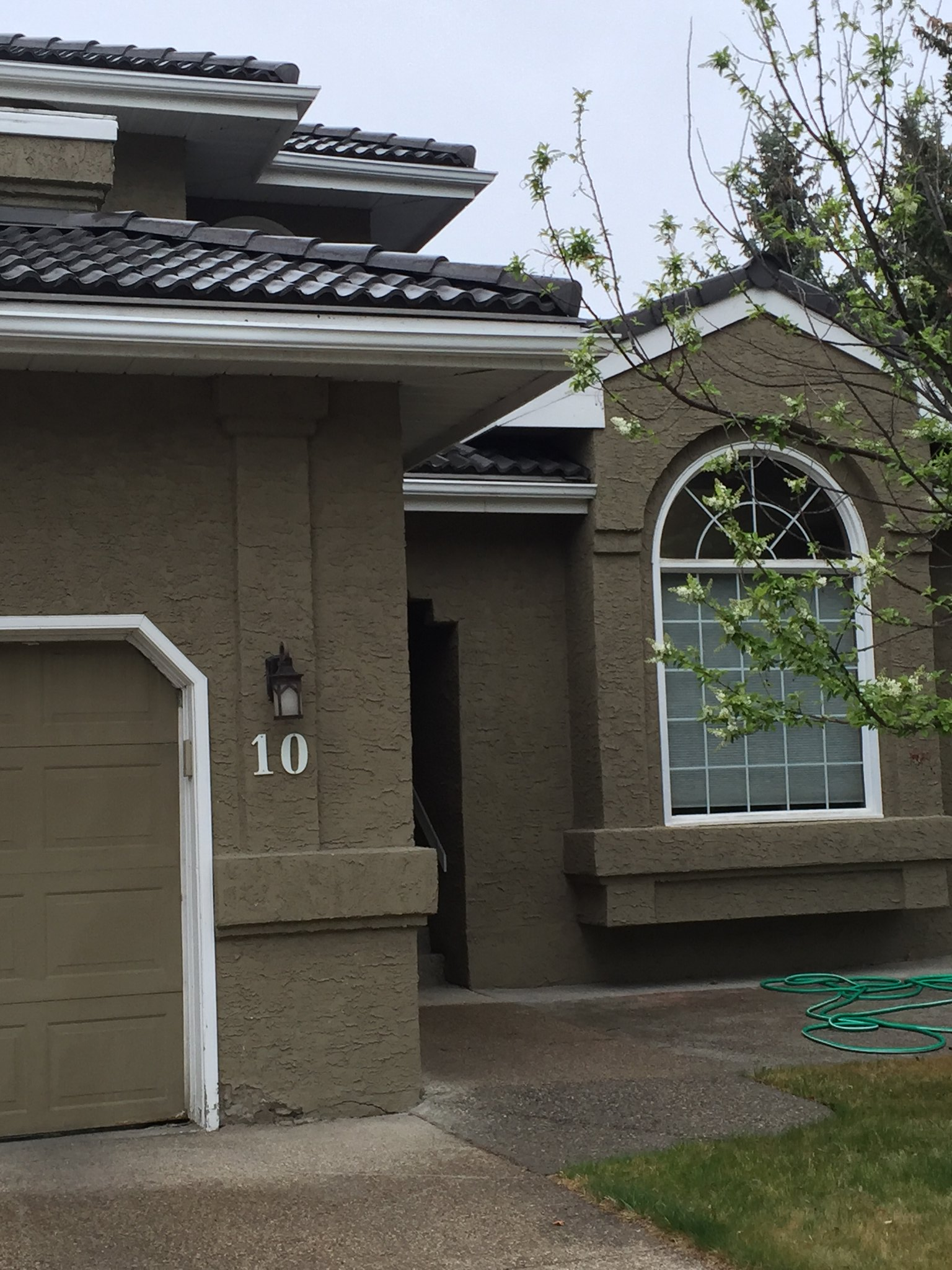 stucco exterior painted warm brown with white soffit and facia