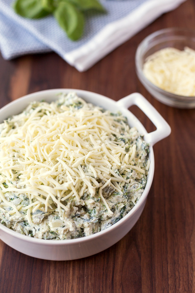 spinach and artichoke dip in pan with shredded mozzarella