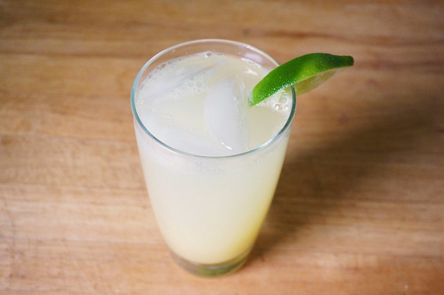 A glass of ginger beer, viewed from above, its lime wedge aligning with the shadow from the sun