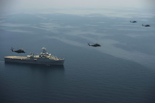 CH-53's from HM-15 fly in formation over the USS Ponce in a multilateral exercise.