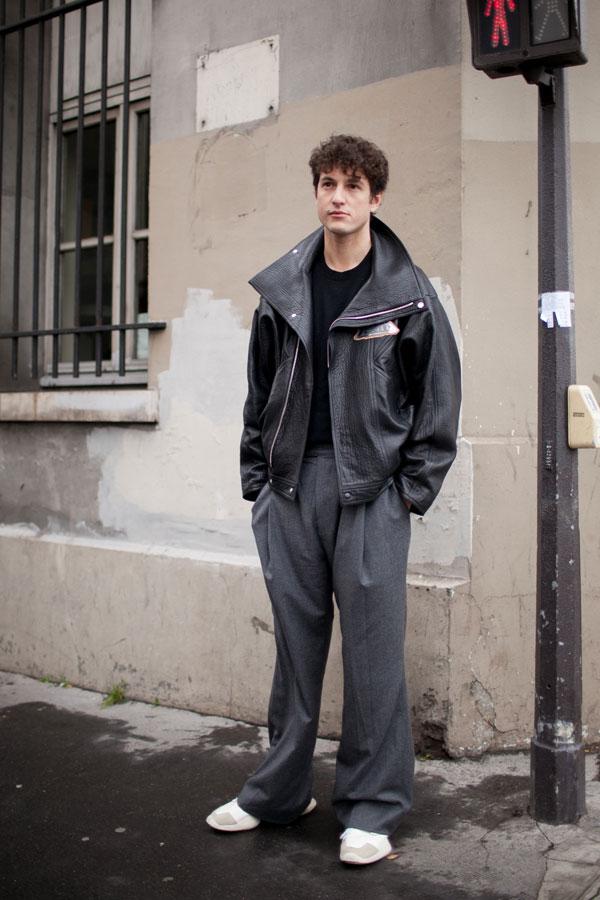 ダブルライダース型レザージャケット×黒Tシャツ×グレーワイドパンツ×白スニーカー