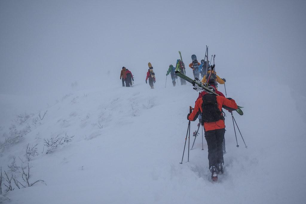 Lines of intrepid skiers hiking to the top of Mt. Annupuri (Niseko, Hokkaido, Japan)